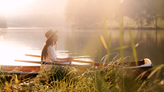slow motion young woman in a boat on the lake - white dress stock videos & royalty-free footage