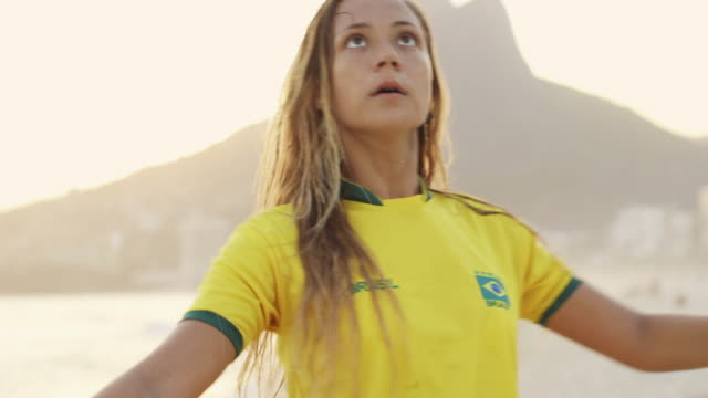 ms a young woman in a brazil t-shirt plays with a football on ipanema beach / rio de janeiro, brazil - juggling stock videos & royalty-free footage