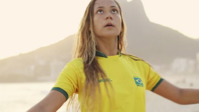 vidéos et rushes de ms a young woman in a brazil t-shirt plays with a football on ipanema beach / rio de janeiro, brazil - brésilien