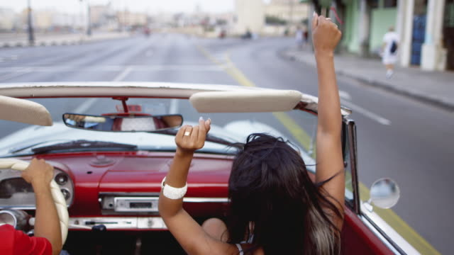 vidéos et rushes de ms a young woman in a convertible dances to music / havana, cuba - cuba