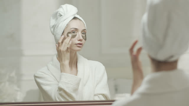 young woman in a dressing gown and a towel adjusts the medical eye patch under her eyes and looks at herself in the mirror. - medical dressing stock videos & royalty-free footage