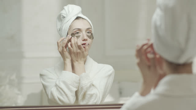 young woman in a dressing gown and a towel puts on medical eye patch under her eyes and looks at herself in the mirror. - medical dressing stock videos & royalty-free footage