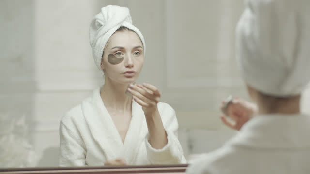 young woman in a dressing gown and a towel removes the medical eye patch from under her eyes and looks at herself in the mirror. - medical dressing stock videos & royalty-free footage