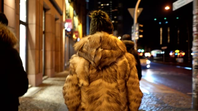 young woman in a fur coat on the street at night - winter coat stock videos & royalty-free footage