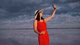 young woman in a hat and sunglasses takes a selfie on a background of sky and clouds. Traveler takes photos on the phone camera