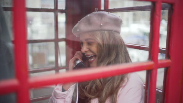 a young woman in a london red telephone box. - 電話ボックス点の映像素材/bロール