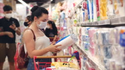 Young woman in a mask from a coronavirus epidemic makes purchases in a supermarket, chooses toilet paper, people in a panic from the global epidemic are buying up everything.