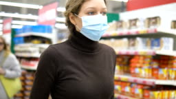 A young woman in a medical mask walks with a grocery cart in a supermarket, close-up