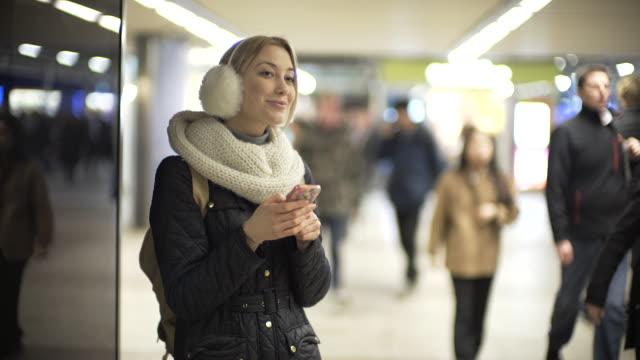 vídeos de stock, filmes e b-roll de a young woman in a station calling and texting. - protetor de ouvido