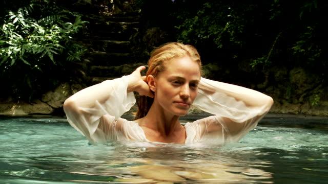 Jovem mulher em uma piscina tropical