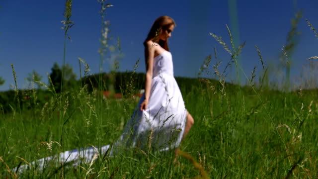 vidéos et rushes de une jeune femme dans une robe blanche sur le terrain. - robe blanche