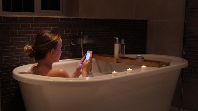 young woman in bath using phone - candlelight stock videos & royalty-free footage