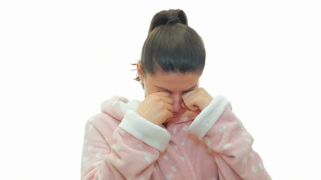 vídeos de stock, filmes e b-roll de mulher jovem em roupão bocejando no fundo branco. - mãos cobrindo boca