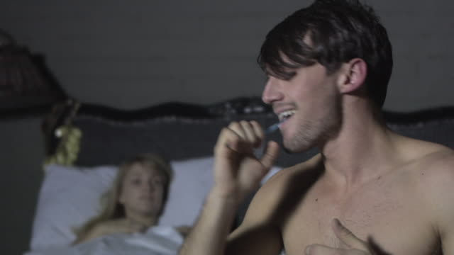 stockvideo's en b-roll-footage met young woman in bed and young man brushing teeth - dubbel bed