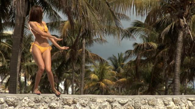 slo mo ws young woman in bikini hula dancing along the top of a stone wall / palm trees in background / south beach, florida - bikini top stock videos & royalty-free footage