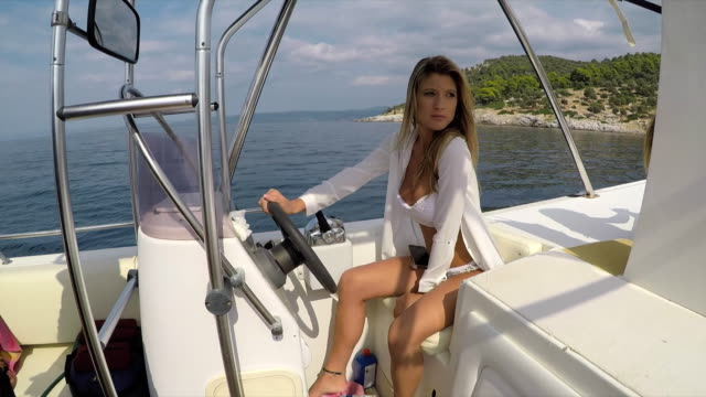 young woman in bikini riding motor boat - captain stock videos & royalty-free footage