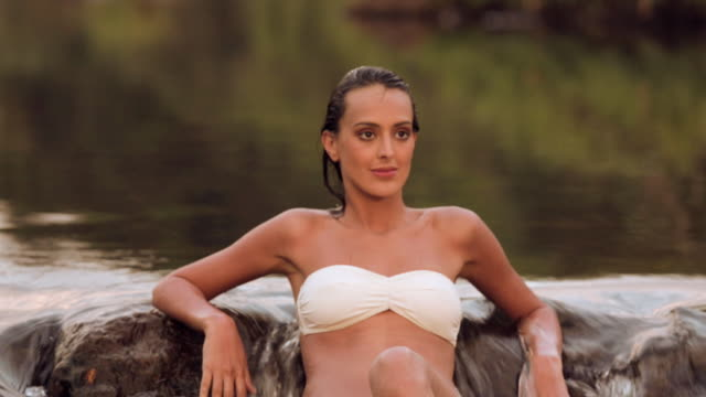 young woman in bikini sitting at waterfall, athirappilly, kerala, india - wet hair stock videos and b-roll footage