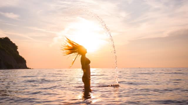 Jonge vrouw in bikini opspattend water van de oceaan met haar bij zonsondergang