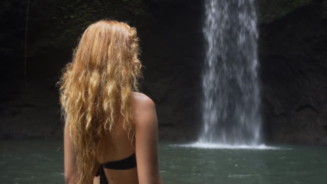 Young woman in bikini standing in water, admiring a waterfall