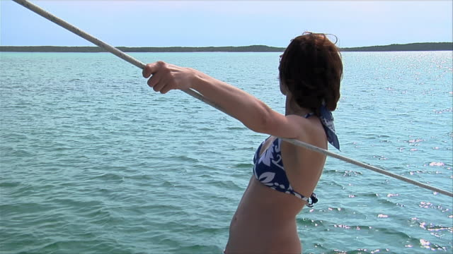 ms, young woman in bikini standing on boat, harbour island, bahamas  - hair accessory stock videos & royalty-free footage
