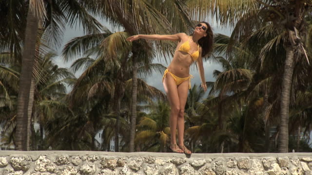 slo mo ws young woman in bikini standing on wall with arms outstretched enjoying the sunshine / palm trees in background / south beach, florida - bikini stock-videos und b-roll-filmmaterial