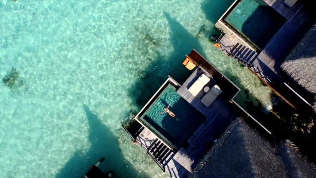 AERIAL: Young woman in bikini swimming in ocean front villa pool and looking towards the sea horizon