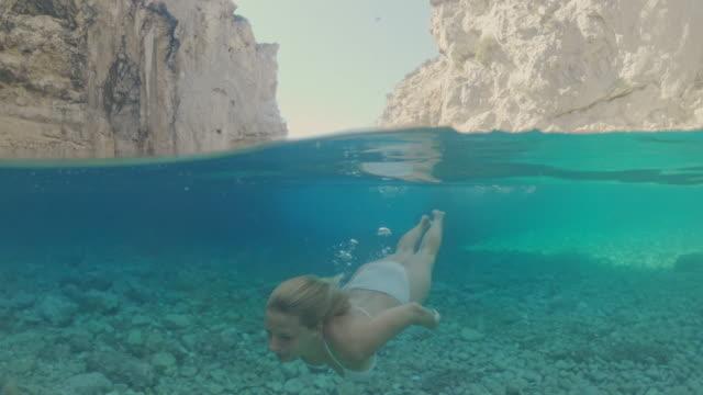 アドリア海、クロアチアで水中で泳ぐビキニのms若い女性 - 水中カメラ点の映像素材/bロール
