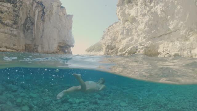 岩のアドリア海、クロアチアで水中を泳ぐビキニのms若い女性 - 水中カメラ点の映像素材/bロール