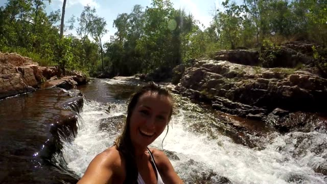 Jonge vrouw in bikini neemt een selfie met watervallen