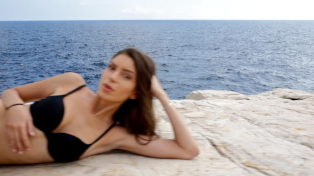 young woman in black bikini on coastline lying on side and posing - lying on side stock videos & royalty-free footage