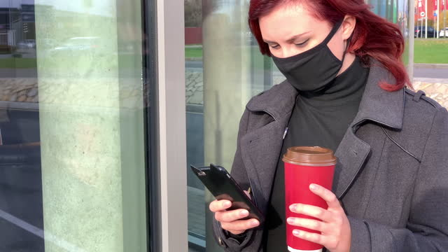 vídeos de stock, filmes e b-roll de young woman in black face mask holds coffee cup and uses smartphone near hospital - evitar os outros