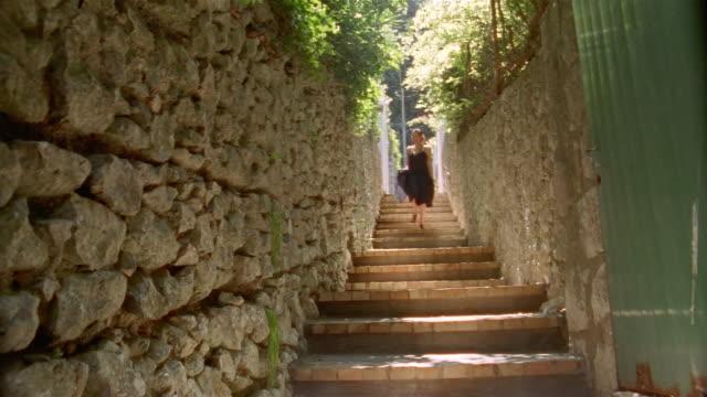 stockvideo's en b-roll-footage met young woman in black sundress running down steps in alleyway / capri - zonnejurk