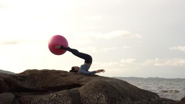 vidéos et rushes de jeune femme en body pratiquant le yoga sur une colline rocheuse . - belle femme