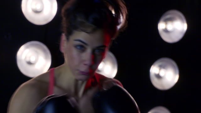 young woman in boxing gloves punches at camera in slow motion 4k - vesper stock stock videos & royalty-free footage