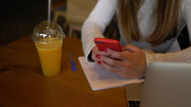 vídeos y material grabado en eventos de stock de mujer joven en mensajes de texto de café - zumo de naranja