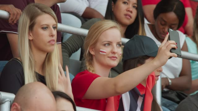 young woman in cheering outfit taking a selfie on the tribune while waiting for the game to start - portability stock videos & royalty-free footage