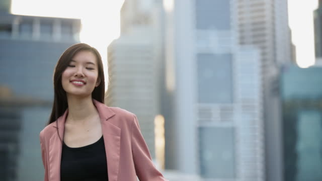 ms young woman in city with sun on buildings behind her - asia stock videos & royalty-free footage