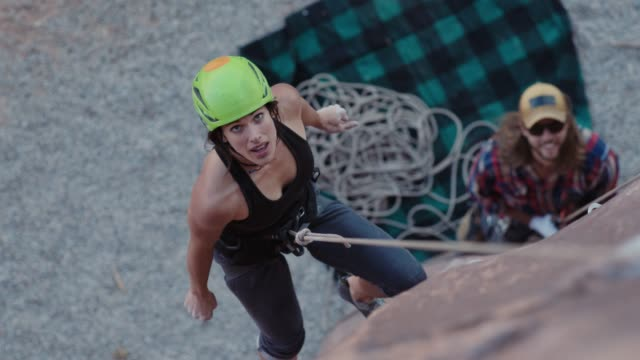 stockvideo's en b-roll-footage met slo mo. young woman in climbing harness looks up at rock face on moab adventure. - boulder rock