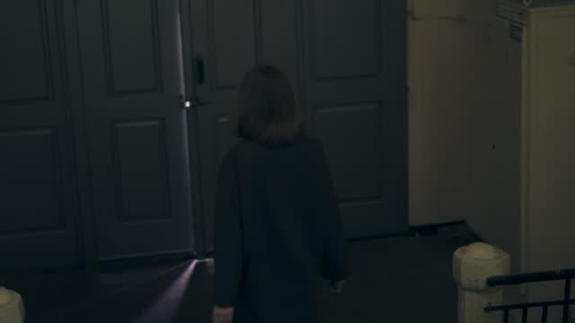古い家を出るコートの若い女性 - 建物入口点の映像素材/bロール