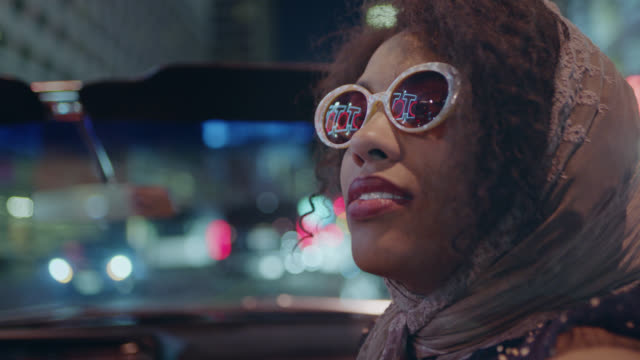 CU. Young woman in convertible looks up with sunglasses reflecting neon casino lights.
