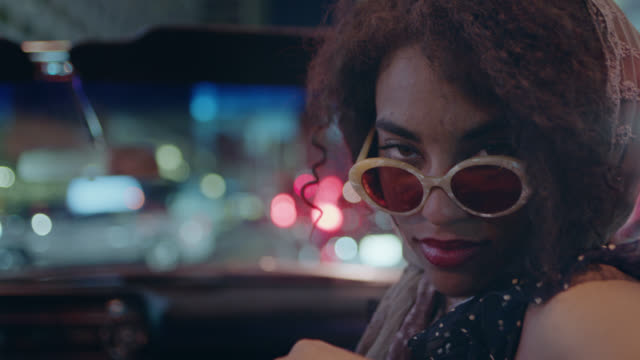 vidéos et rushes de cu. young woman in convertible lowers sunglasses to stare at camera and laughs. - hipster personne