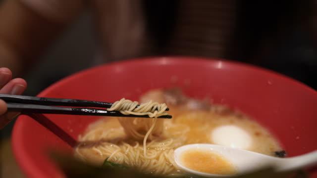 東京で日本のラーメンを食べる眼鏡をかけたcu若い女性 - 高級グルメ点の映像素材/bロール