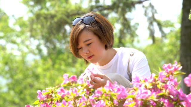 young woman in flower garden enjoys nature - 中国人点の映像素材/bロール
