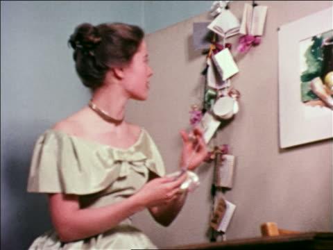 vídeos y material grabado en eventos de stock de 1951 young woman in formalwear hanging cards on strings / educational - sólo una adolescente