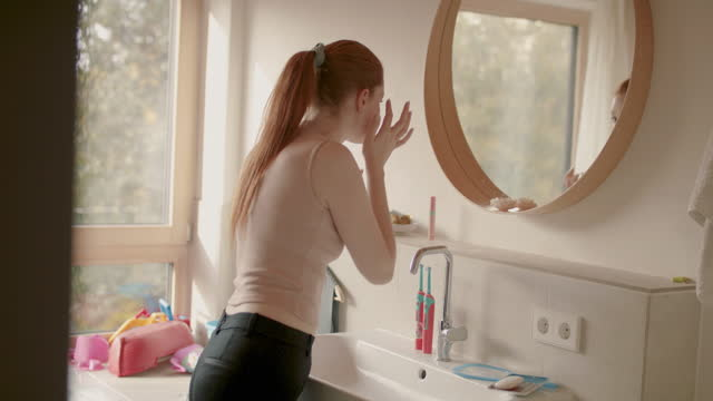 young woman in front of mirror in bathroom in morning - in front of stock videos & royalty-free footage