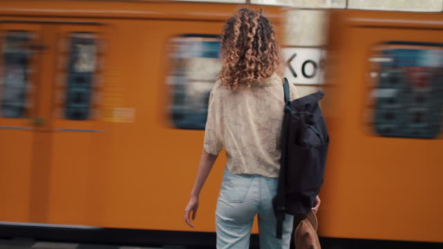 young woman in front of moving train on platform in berlin - jeans stock videos & royalty-free footage