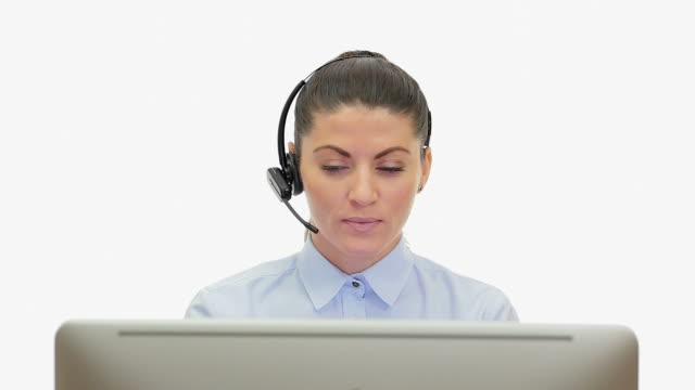 young woman in front of the computer talking over the headset. - computer monitor white background stock videos & royalty-free footage