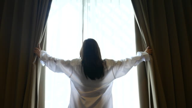 young woman in front of the window raising her hands, lifestyle conncept - curtain stock videos & royalty-free footage