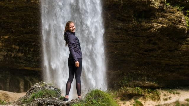 振り返ってみると笑顔の滝の前で若い女性