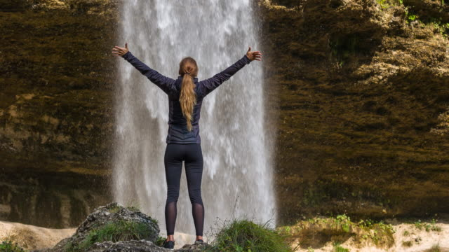 young woman in front of waterfall with her arms outstretched - winnings stock videos and b-roll footage